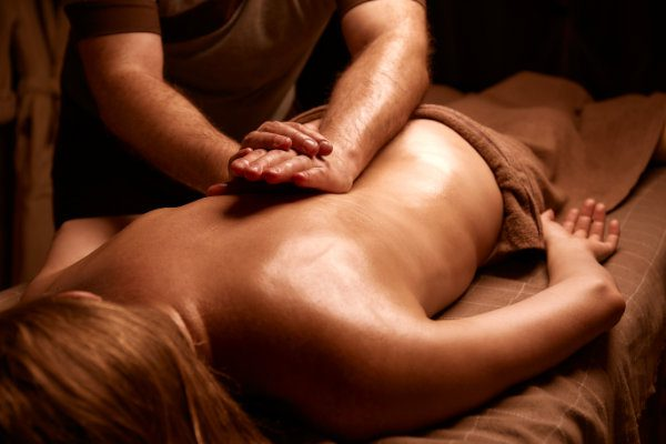 Back massage in the spa salon. Muscle recovery after exercise. Wellness. Back treatment. sports massage. The masseur does a back massage. Dim light in the spa. Masseur's hands